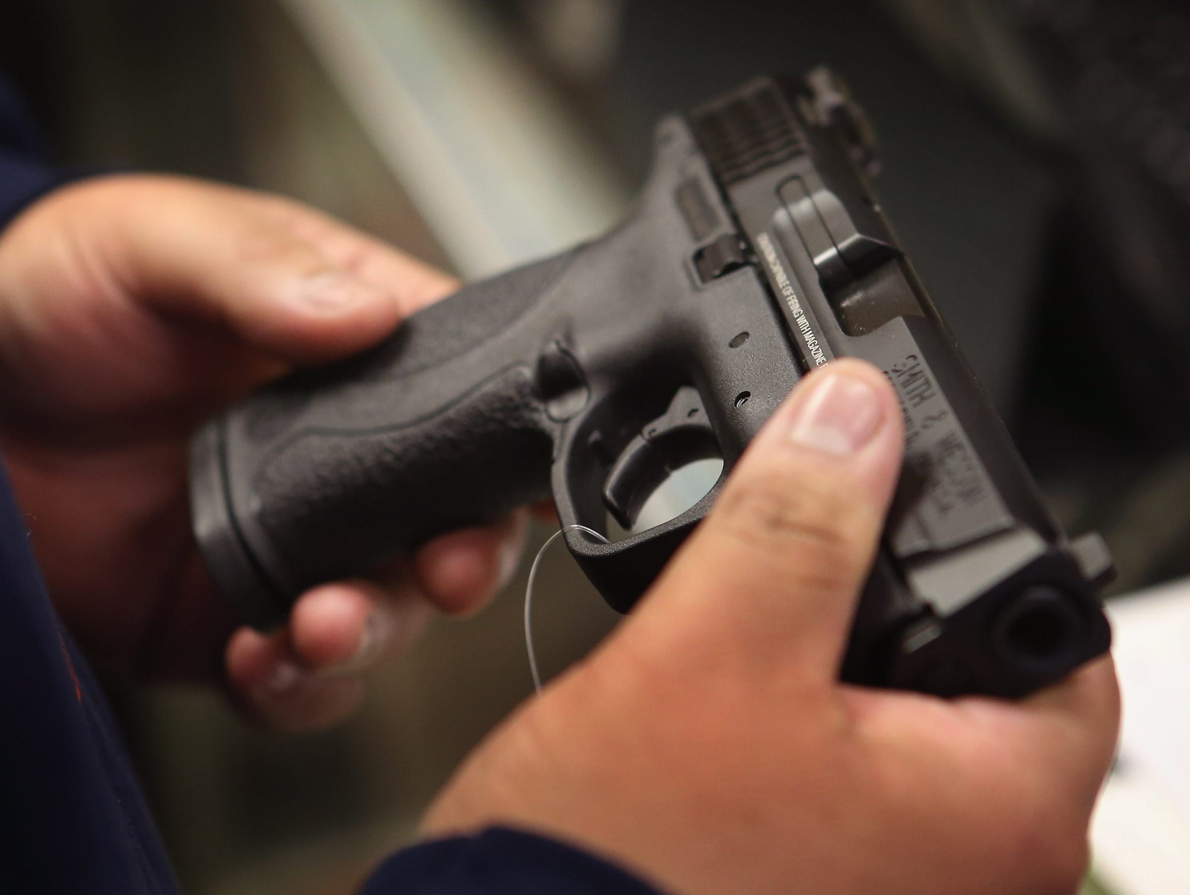 A customer shops for a pistol at an Illinois sporting