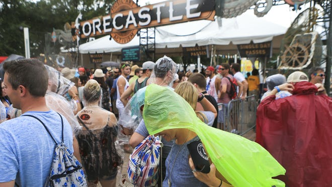 Rose Ann Byers puts on a rain slicker while waiting outside the west entrance of Forecastle Festival in 2016 after the festival was evacuated due to bad weather.