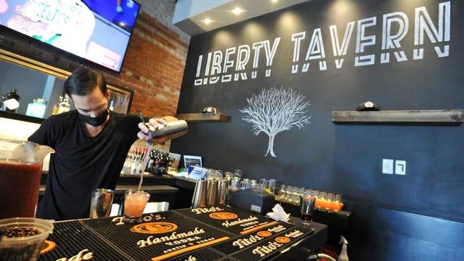 Liberty Tavern co-owner, Evan Harrington, mixes a drink at the bar at the new the Liberty Tavern on Hancock Street in Quincy, Sunday, Aug. 23, 2020.