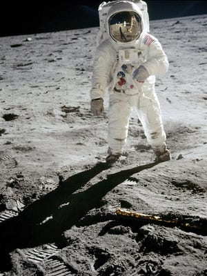 """Astronaut Neil Armstrong's famous """"visor"""" photo from the Apollo 11 mission captures fellow astronaut Buzz Aldrin on the moon's surface, his gold-plated sun visor reflecting Armstrong and their lunar module."""
