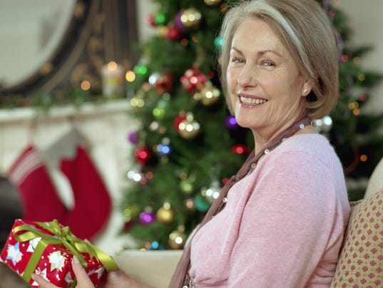 Senior woman holding christmas present, smiling, portrait