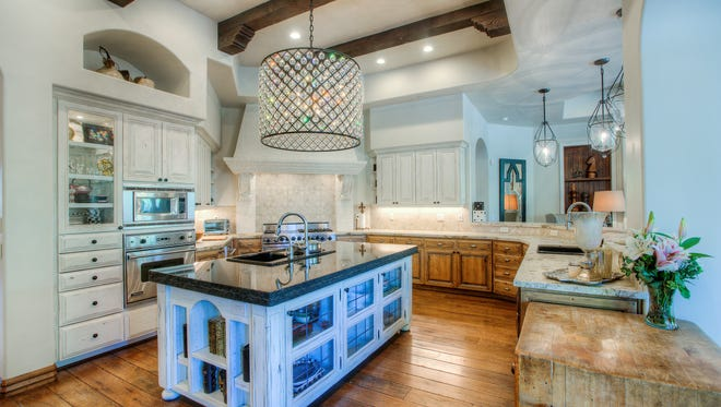 The gourmet chef's kitchen features Alder two-toned cabinets, granite counter tops, a huge island, two sinks and stainless steel appliances.