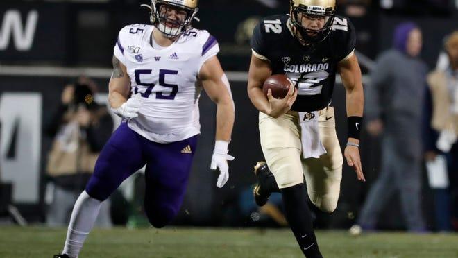 Colorado quarterback Steven Montez runs for a short gain as Washington linebacker Ryan Bowman pursues during the first half of an NCAA college football game Saturday, Nov. 23, 2019, in Boulder, Colo. (AP Photo/David Zalubowski)