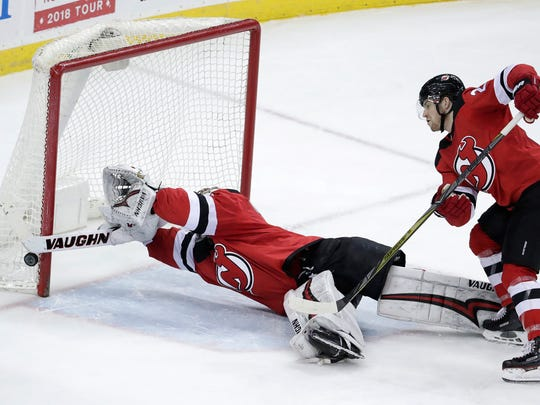 New Jersey Devils goaltender Keith Kinkaid, left, dives to make a save on a shot by Tampa Bay Lightning defenseman Ryan McDonagh, not seen, during the third period of an NHL hockey game Saturday, March 24, 2018, in Newark, N.J. Devils' Damon Severson helps defend on the play. The Devils won 2-1.