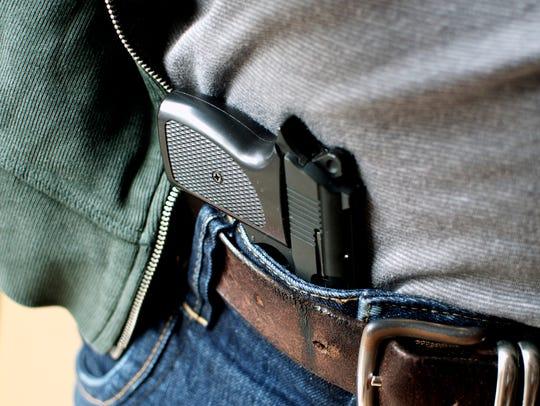 Gun tucked in a belt pistol being concealed.
