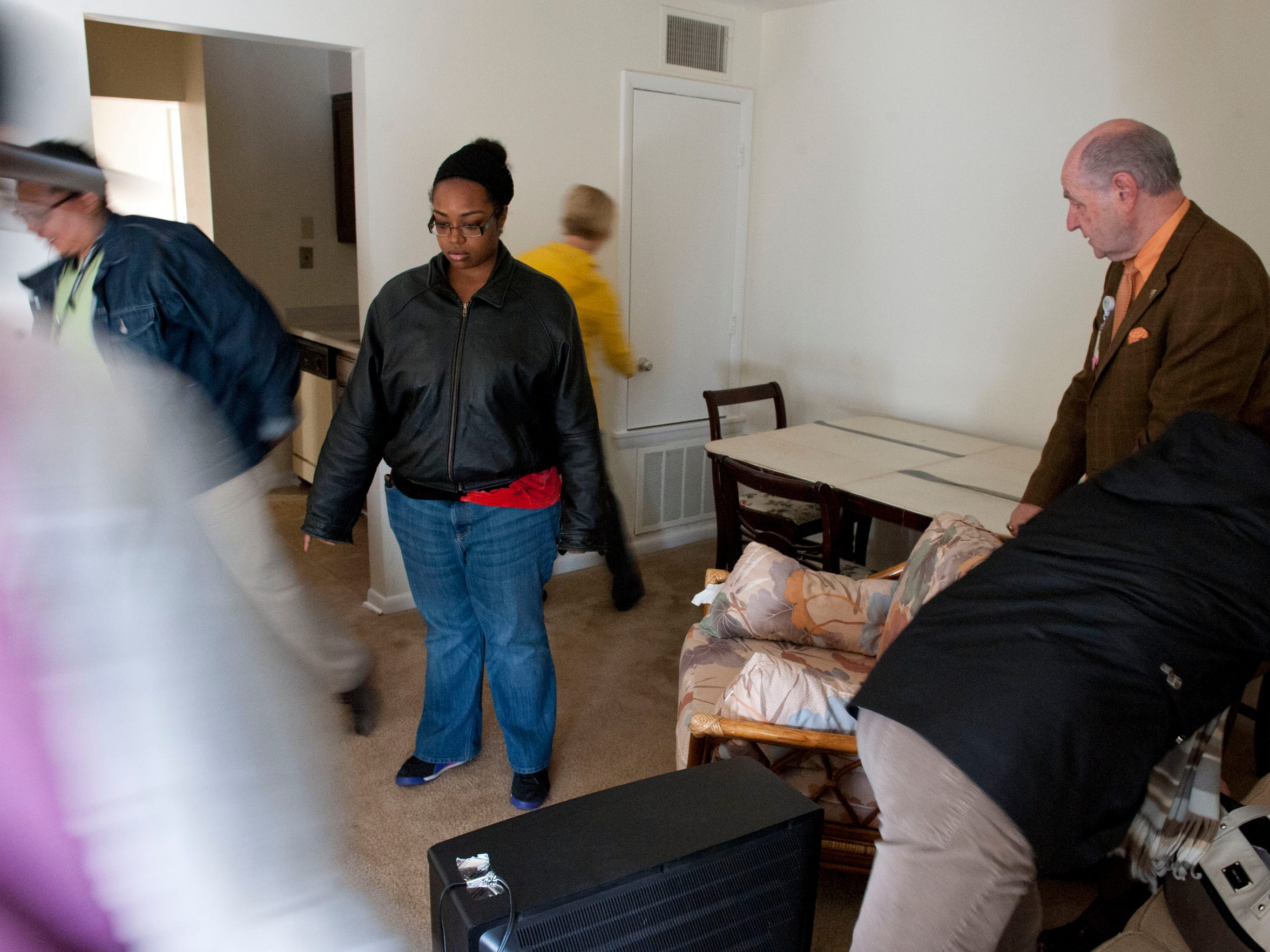 Jessica duCille watches as workers help arrange furniture in a new apartment.