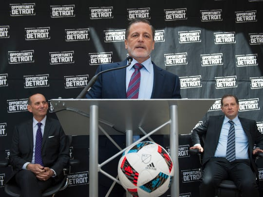 Dan Gilbert, flanked by MLS commissioner Don Garber, left, and Arn Tellem (standing in for Platinum Equity owner Tom Gores), presents a vision of building a multi-use soccer stadium at the stalled Wayne County Jail construction site in downtown Detroit on April 27, 2016.