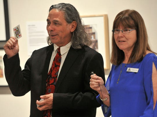 Artist David Diaz holds up a card during a drawing Thursday evening at the National Center for Children's Illustrated Literature Sept. 14, 2017. Beside him is Debbie Lillick, executive director for the NCCIL.