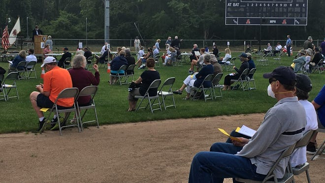 Chatham voters sit spaced across the outfield at Veterans Field for the annual town meeting Monday night.