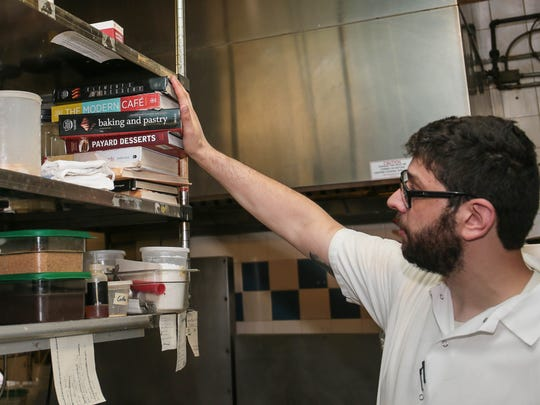 Pastry Chef Ben Deutsch with some of his reference books at The Frog and The Peach in New Brunswick on July 26, 2016.