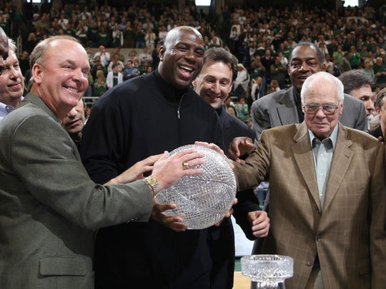 "FILE - In this Feb. 22, 2009, file photo, members of Michigan State's 1979 NCAA championship basketball team, including front row from left, Jay Vincent, Terry Donnelly, Earvin ""Magic"" Johnson, coach Jud Heathcote and Gerald Gilkie, hold the championship trophy during a ceremony commemorating the 30th anniversary of the event during halftime of an NCAA college basketball game between Michigan State and Wisconsin in East Lansing, Mich. Heathcote, who led Michigan State and Magic Johnson to the 1979 NCAA championship, has died. He was 90. The school says Heathcote died Monday, Aug. 28, 2017, in Spokane, Washington. (AP Photo/Al Goldis, File)"
