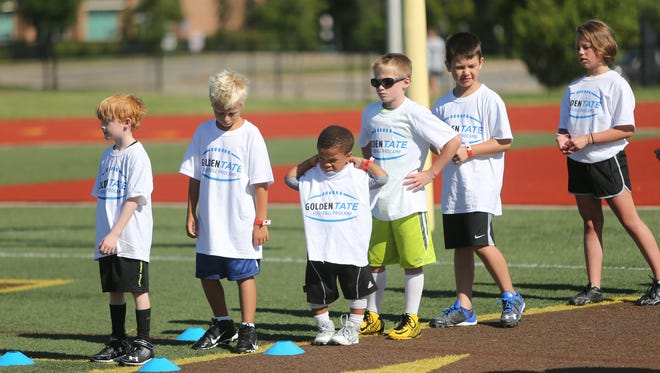 Campers line up for drills during the Golden Tate ProCamp on July 30, 2015, at Rochester Adams.