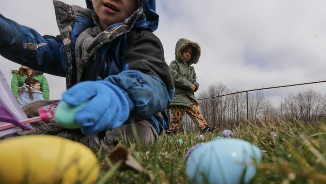 Josiah Bratcher, 4, of Flint, right, searches for candy-filled plastic eggs as Jacob Medrano, 4, of Flint picks one up during an Easter egg hunt on Friday, March 25, 2016, put on by the Community Impact Church at the Fraternal Order of Police Lodge 126 in Flint.