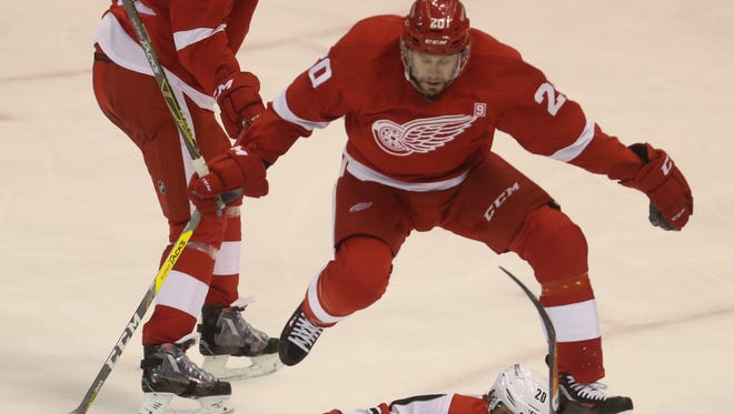 Red Wings forward Drew Miller goes for the puck against the Hurricanes' Sebastion Aho during the third period of the Wings' 4-2 win Tuesday at Joe Louis Arena.