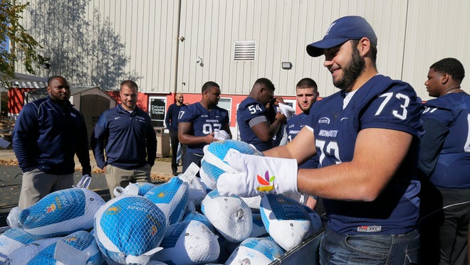 Monmouth University football team player Gianni Mazzone helps unload frozen Thanksgiving turkeys at The FoodBank of Monmouth and Ocean Counties in Neptune, NJ Thursday, November 17, 2016.