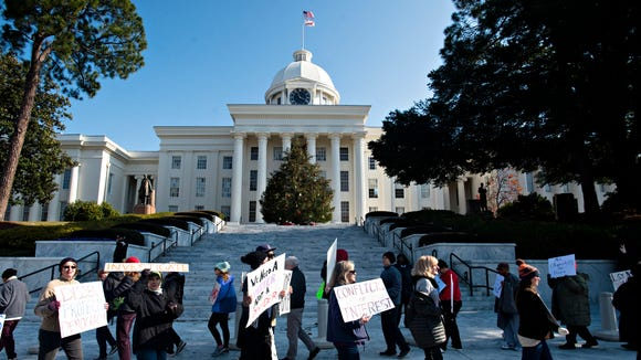 Protestors march outside the Alabama Capitol building requesting that electoral college delegates abstain from voting for President elect Donald Trump on Monday, Dec. 19, 2016, in Montgomery, Ala.
