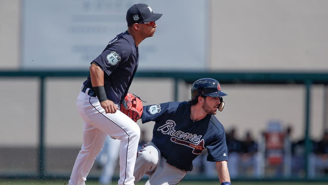 Tigers shortstop Jose Iglesias (left) looks on as Braves shortstop Dansby Swanson (right) slid safely into second base on a grounder to first base during the first inning of the Tigers' 10-7 exhibition win Monday in Lakeland, Fla.