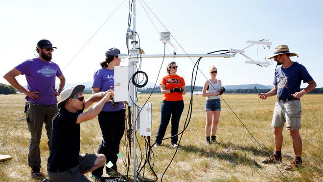 A team of scientists and college students work to install one of 16 instrument positions that will gather data during Monday's solar eclipse from a field south of Corvallis, Oregon, on Saturday, Aug. 19, 2017