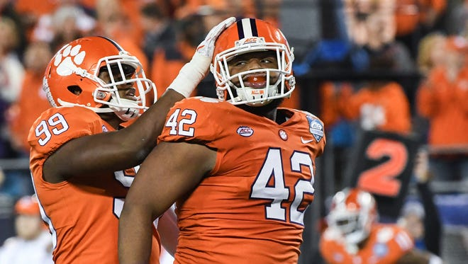 Clemson defensive end Clelin Ferrell (99) congratulates Christian Wilkins (42) on his sack during the second quarter of the Dr.Pepper ACC football championship in Charlotte on Saturday.