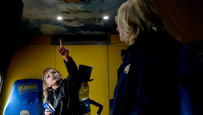 Sylvia Serna, 9, left, gets a tour of the NUTmobile with Planters' Peanutter Dakota Connell-Ledwon on Thursday in Anderson.