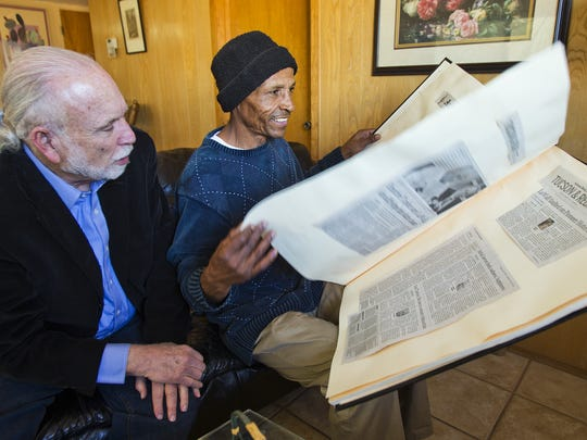 In 2013, Louis Taylor (right) looks through a scrapbook of his time in prison.