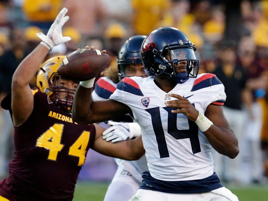 FILE - In this Nov 25, 2017, file photo, Arizona quarterback Khalil Tate (14) throws while getting pressured by Arizona State linebacker Alani Latu during the second half of an NCAA college football game, in Tempe, Ariz. Tate went from starting last season as a backup quarterback to putting himself into the Heisman Trophy conversation with a stretch of eye-popping games (AP Photo/Rick Scuteri, File)
