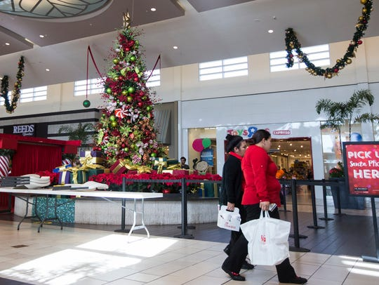 People walk past holiday decorations as they shop at