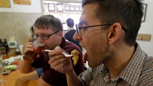 Stephen Baker, left, drinks a beer while his brother Daniel Baker, eats pie at the Epic Brewery during pie and beer day Friday in Salt Lake City. Research released Friday shows people have a taste for fat.