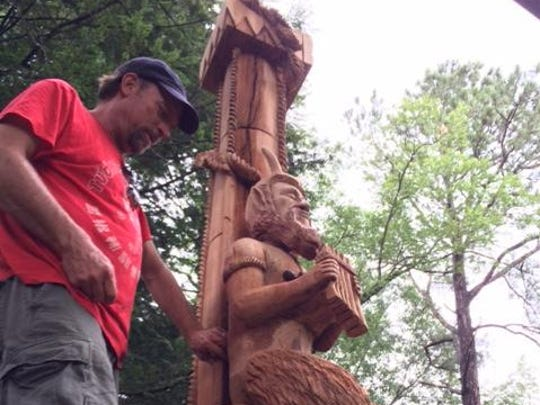 Wood carver Jack Bailey is putting the finishing touches on a work depicting Pan, the Greek god of rustic music, forests and fertility at Howard Hanger's home in Chicken Hill.