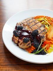 Pork porterhouse with a blackberry chipotle glaze.