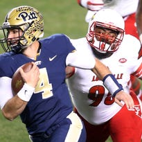 Pittsburgh Panthers quarterback Nathan Peterman (4) runs the ball past Louisville Cardinals defensive end Sheldon Rankins (98)   during the third quarter at Heinz Field.