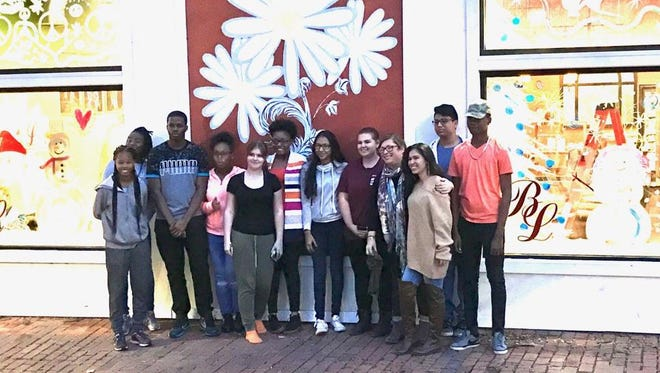 Poughkeepsie High School Art Club students stand in front of Bella Luci Salon where they painted the windows Dec. 6 for the holiday season.