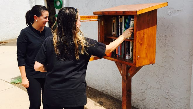 Natalie Bustamante (right) returns a book to a little free library owned by Elizabeth Aguilar-Barnett in a Tempe neighborhood.