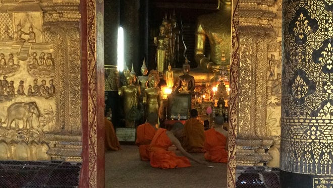 Monks worship at day's end inside a monastery in Luang Prabang, Laos.