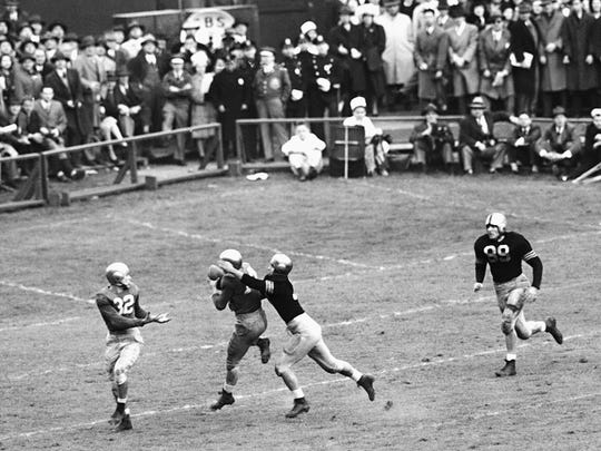 FILE - In this Nov. 9, 1946, file photo, Notre Dame's Emil Sitko (14) grabs a pass intended for Army's Bill West, center right, during the fourth quarter of a college football game at Yankee Stadium in New York. Notre Dame quarterback John Lujack (32) holds out his hands for a possible lateral. The game ended in a scoreless tie.