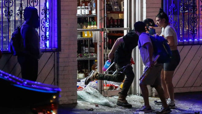 A liquor store at E. Sixth Street and Interstate 35 is looted during a protest in downtown Austin early Monday.