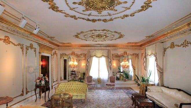 The ceiling, walls and window casings in the living room  are gold leaf hand-laid over plaster molding.
