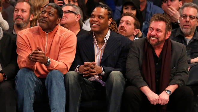 Larry Johnson and Latrell Sprewell look on with New York Knicks executive chairman James Dolan during the second half against the San Antonio Spurs at Madison Square Garden.