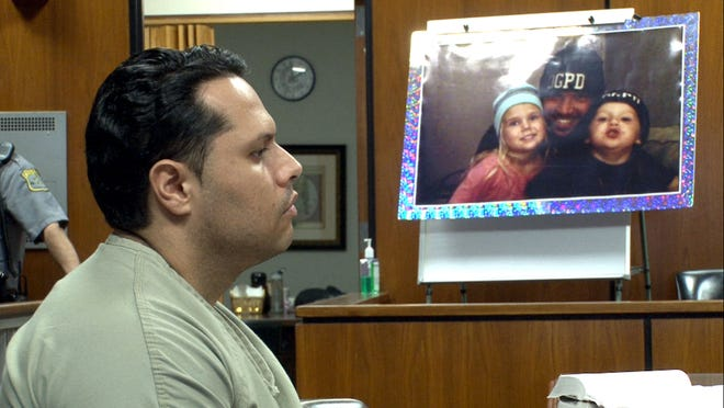 Erick Uzcategui sits in state State Superior Court Wednesday, near a picture of Ocean Gate police Officer Jason Marles and his children in the background. Uzcategui was found guilty of the vehicular homicide in the death of Marles.