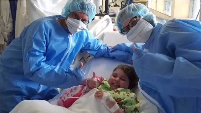 Marisa Tufaro, flanked by her parents, Greg (left) and Cyndi, gives a thumbs up before her July 2016 heart transplant surgery.