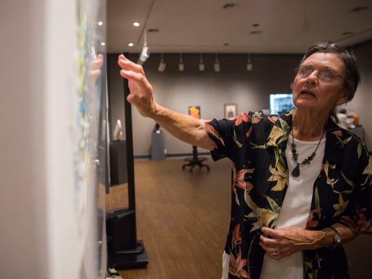 """Joanna Sunshine, an Isles of Capri artist being featured as the """"paper"""" aspect in the Marco Island Center for the Arts Rock Paper Scissors Exhibition explains one of her art pieces on display in the gallery on Friday, May 4, 2018."""