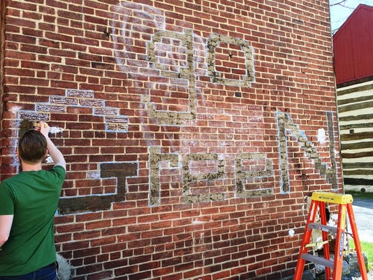 Craig Walt paints the Go Green logo with living moss on the CoWork155 building during the Go Green in the City street fair Saturday. Passersby will be able to see the moss grow on the building in the next few weeks.