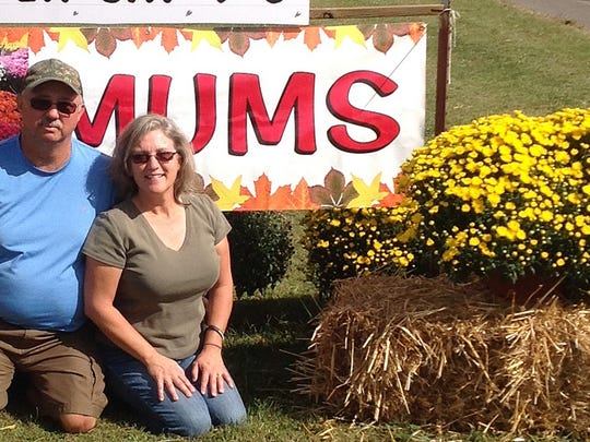 Lisa Wright and her husband, Dean, display one of the mums grown in their gardens.