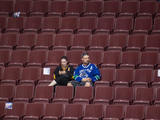 Vancouver Canucks fans sit in the stands after the team defeated the Edmonton Oilers in their final NHL hockey game of the season, Saturday, April 9, 2016, in Vancouver, British Columbia. (Darryl Dyck/The Canadian Press via AP)