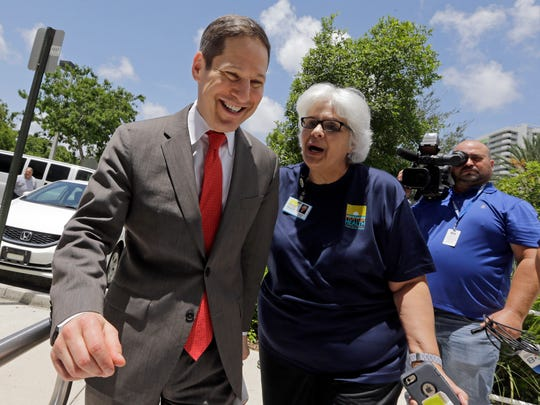 Centers for Disease Control and Prevention Director Dr. Tom Frieden, left, talks to Dr. Lillian Rivera, administrator of the Florida Department of Health in Miami-Dade County, as he arrives at the Department of Health on Thursday, Aug. 4, 2016, in Miami. Frieden said aerial spraying of the insecticide naled is killing many mosquitoes in a Miami neighborhood where the insects apparently transmitted Zika to 15 people.