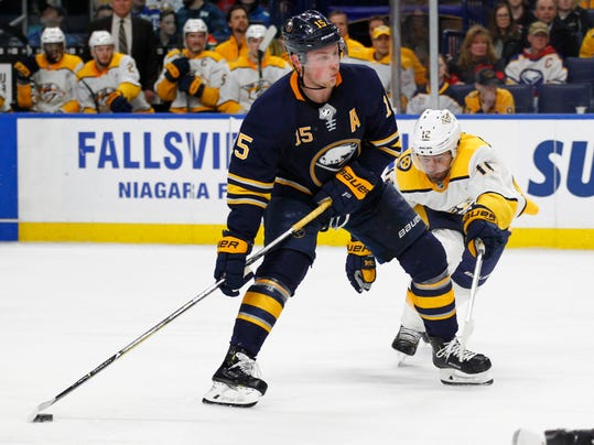 "FILE - In this March 19, 2018, file photo, Buffalo Sabres' Jack Eichel (15) carries the puck past Nashville Predators' Mike Fisher (12) during the third period of an NHL hockey game in Buffalo, N.Y. Eichel has difficulty assessing the sorry state of the Sabres, who haven't had a sniff at the playoffs in the three years since his celebrated arrival. ""When I got drafted, if you would've said we'd be in this position, I probably would've told you to give your head a shake,"" Eichel told The Associated Press. (AP Photo/Jeffrey T. Barnes, File)"