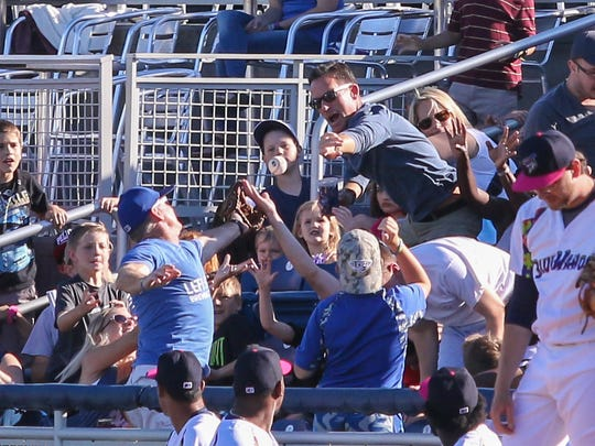 Fans along the first base line try to catch a foul ball hit by Tennessee's Carlos Penalver Sunday afternoon at Blue Wahoos Stadium.