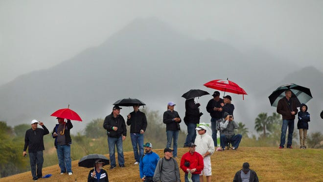 Fans watch golf with the McDowell Mountains, shrouded in clouds, serving as the backdrop during the second round of the Waste Management Phoenix Open at TPC Scottsdale on Jan. 30, 2015.
