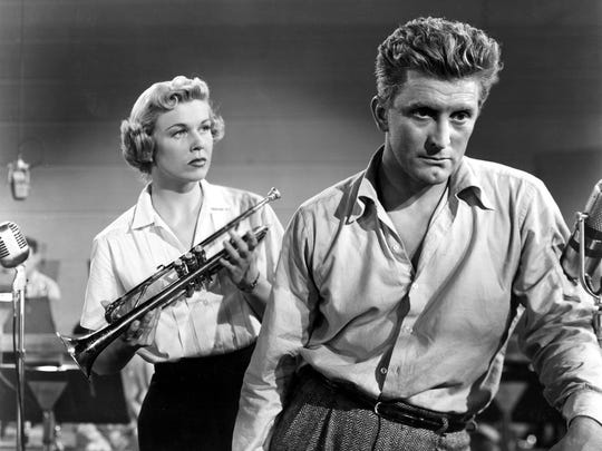 "Doris Day stands by Kirk Douglas in the 1950 movie ""Young Man With a Horn."""
