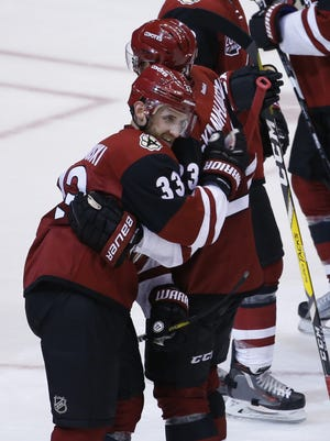Coyotes' Oliver Ekman-Larsson (23) celebrates scoring the game-winning goal with Alex Goligoski (33) in the overtime period on opening night at Gila River Arena on October 15, 2016 in Glendale, Ariz.